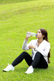 Sporty woman sitting and get refreshment after workout Royalty Free Stock Photo