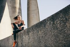 Sporty woman sitting outdoors after fitness training stock images