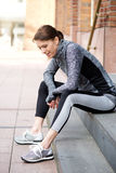 Sporty woman sitting outside resting after workout Royalty Free Stock Images