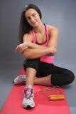 Sporty Woman Sitting on Pink Yoga Mat Stock Photo