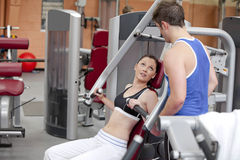 Sporty woman sitting on a shoulder press talking. With her coach in a fitness centre royalty free stock photography