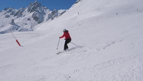 Sporty Woman Skis Carving Down The Slope In The Mountains Ski Resort At Winter. A woman in a red jacket and black trousers skis on the slope alone. She turns stock footage