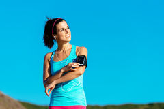 Sporty woman with smartphone armband and earphones Royalty Free Stock Image