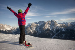 Sporty woman in snowy mountains. Female snowboarder raising her arms expressing happiness Royalty Free Stock Photo