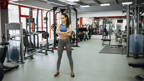 Sporty woman standing with arms crossed in fitness gym. stock image