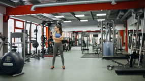 Sporty woman standing with arms crossed in fitness gym. Stock Images