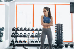 Sporty woman standing with arms crossed in fitness gym. royalty free stock photo