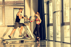 Sporty woman standing near bearded sportsman training on treadmill. Young sporty women standing near bearded sportsman training on treadmill Stock Image