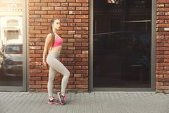 Sporty woman standing near brick wall. Relaxing from jog training, copy space Stock Image