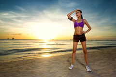 Sporty woman standing by the ocean beach at sunset. Young beautiful sporty woman standing by the ocean beach at sunset Royalty Free Stock Photos