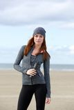 Sporty woman standing outdoors with water bottle Stock Photos