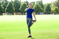 Sporty woman stretching in field Stock Image