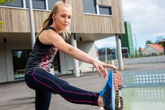 Sporty Woman Stretching Hamstring Leg Muscles Outdoors. Portrait of sporty young woman stretching hamstring leg muscles outdoors Stock Photography