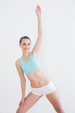 Sporty woman stretching hand in fitness studio Royalty Free Stock Photo