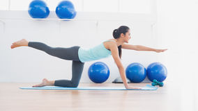 Sporty woman stretching hand and leg in fitness studio Royalty Free Stock Image