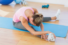 Sporty woman stretching hand to leg in fitness studio Stock Photos