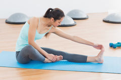 Sporty woman stretching hand to leg in fitness studio Royalty Free Stock Images