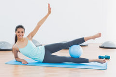 Sporty woman stretching hands in fitness studio Stock Photos
