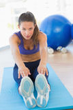 Sporty woman stretching hands to legs in fitness studio Stock Photos