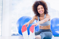 Sporty woman stretching hands to legs in fitness studio Royalty Free Stock Photo