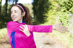 Sporty woman stretching her arm in forest Royalty Free Stock Image