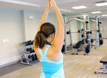 Sporty woman stretching her arm, in a gym. Stock Image