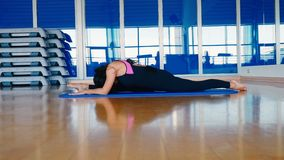 Sporty woman stretching her body in side split and leans to the leg on the mat stock footage