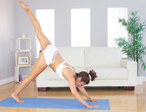 Sporty woman stretching her body with yoga pose on an exercise mat Royalty Free Stock Images
