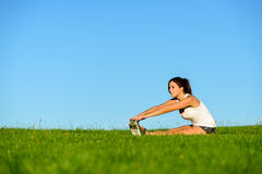 Sporty woman stretching legs outdoor Stock Images