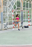 Sporty woman stretching legs before trx outdoor workout Stock Photo