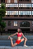Sporty woman stretching and warming up legs before running urban fitness workout. Sport and healthy lifestyle concept. royalty free stock images