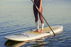 Sporty woman on surf board with paddle. Close up photo. Legs of woman in sportswear standing on stand up paddle board in calm blue river royalty free stock image