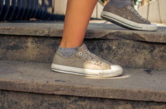 Sporty woman take a step up. Leg of sporty woman wearing sneakers take a step up Royalty Free Stock Photos