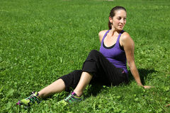 Sporty woman takes a break on a meadow after running Royalty Free Stock Image