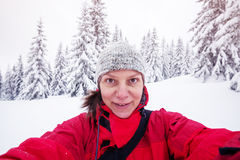 Sporty woman takes selfie in the snow covered forest Stock Images
