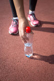 Sporty woman taking bottle of water from running track Stock Photo