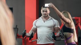 Sporty woman taking selfie with strong man working out in the gym royalty free stock image