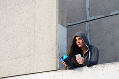 Sporty woman texting on smartphone after urban workout Stock Images
