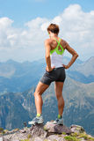 Sporty woman on top of a mountain. Looking while resting Royalty Free Stock Image