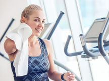 Sporty woman with towel in gym after training Stock Photos