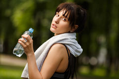 Sporty woman with towel on shoulders holding bottle of water Stock Images