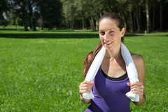 Sporty woman with a towel takes a break during running Royalty Free Stock Images