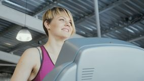 Sporty woman on training apparatus in gym. Close-up. The camera moves from the left to the right. Young woman wearing sporty outfit is in the gym. Sporty young stock video