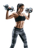 Sporty woman in training pumping up muscles of the back and hands with dumbbells. Stock Image
