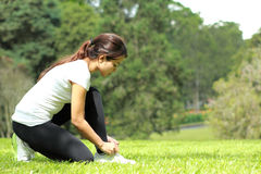 Sporty woman tying her shoelace during workout Royalty Free Stock Images