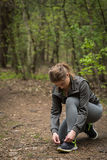 Sporty woman tying shoes Royalty Free Stock Image