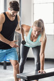 Sporty woman using dumbbells with personal trainor Royalty Free Stock Photography