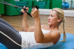 Sporty woman using resistance band in fitness studio Stock Photography