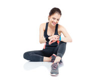 Sporty woman using smart watch. Happy sporty woman sitting on the floor and using smart watch isolated on a white background Stock Image