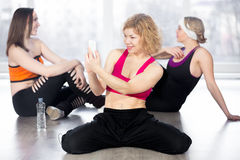 Sporty woman using smartphone on break in fitness class Royalty Free Stock Image